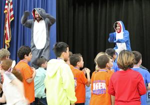 Photo of Tamaques principal David Duelks and media specialist Stephanie Landay-Nesser and other staff members dressed as sharks and dancing to the children's song