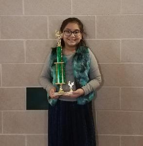 girl poses with the trophy she earned as the spelling bee champion