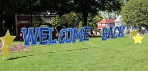 Photo of Welcome Back sign on school front lawn.