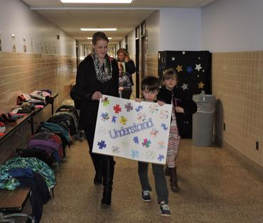 Students carrying autism awareness signs with teacher and class