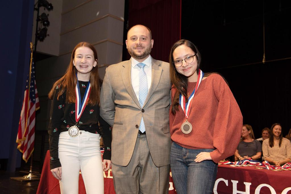 Teacher Joseph Lento presents medals to two seventh graders