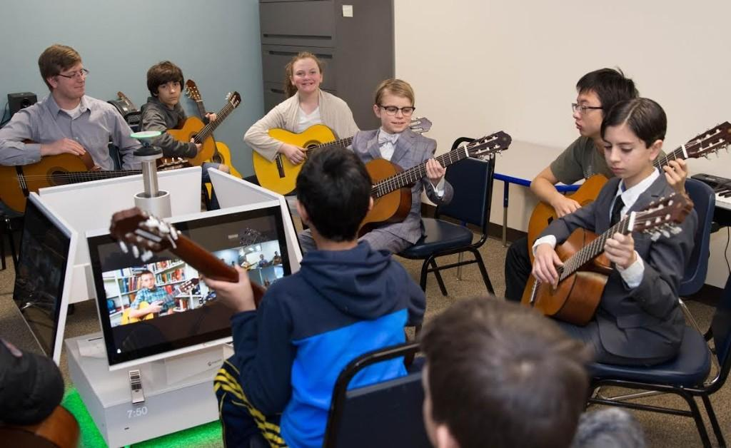 Teacher others to play guitar through synchronous learning