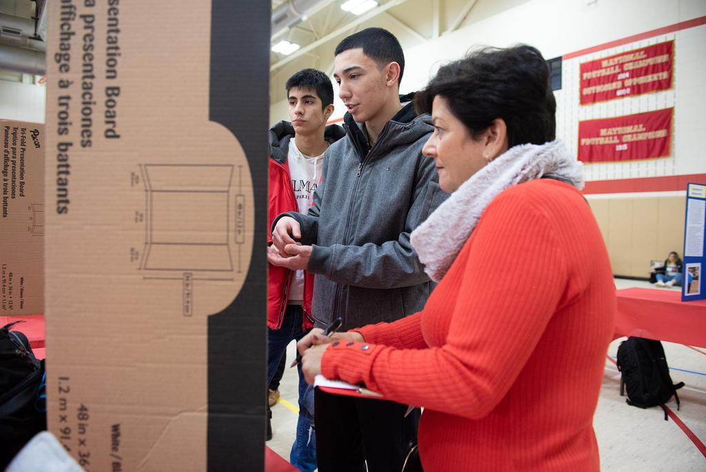 A sideway view of a judge and a student looking at a posterboard