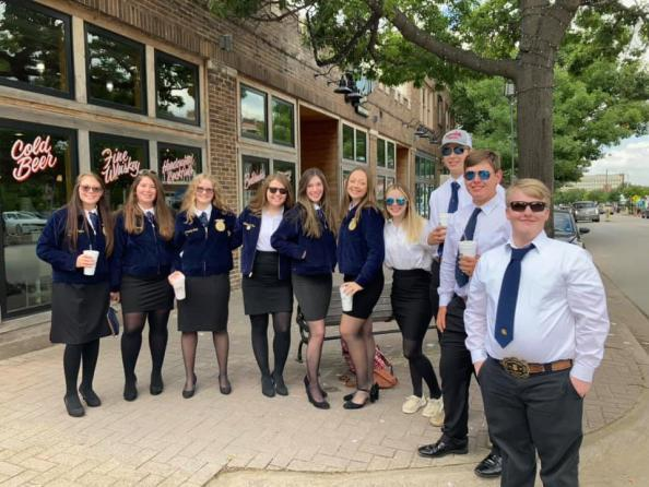 group of teens in matching uniforms outside restaurant