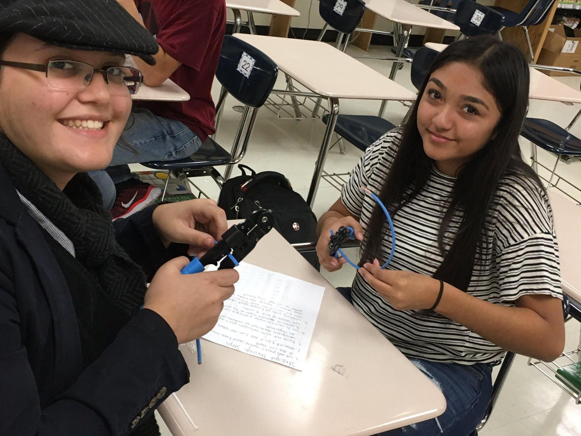 two students holding pliers and snipping a wire