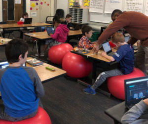 third graders sit on red balls in their classroom