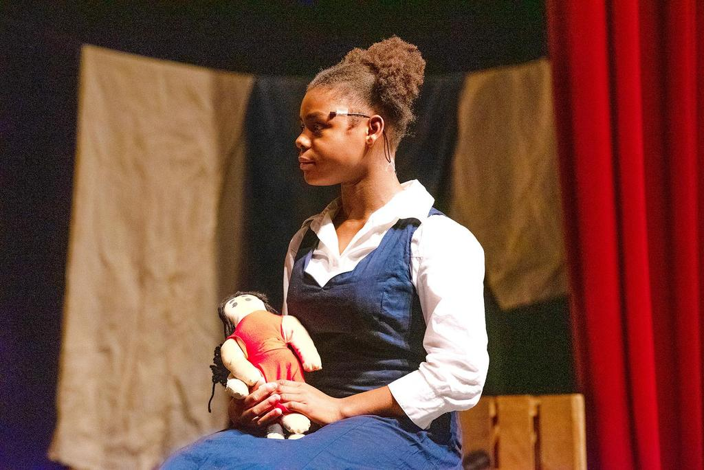 Rae Previlon, playing the role of Little Girl, sits and holds a doll