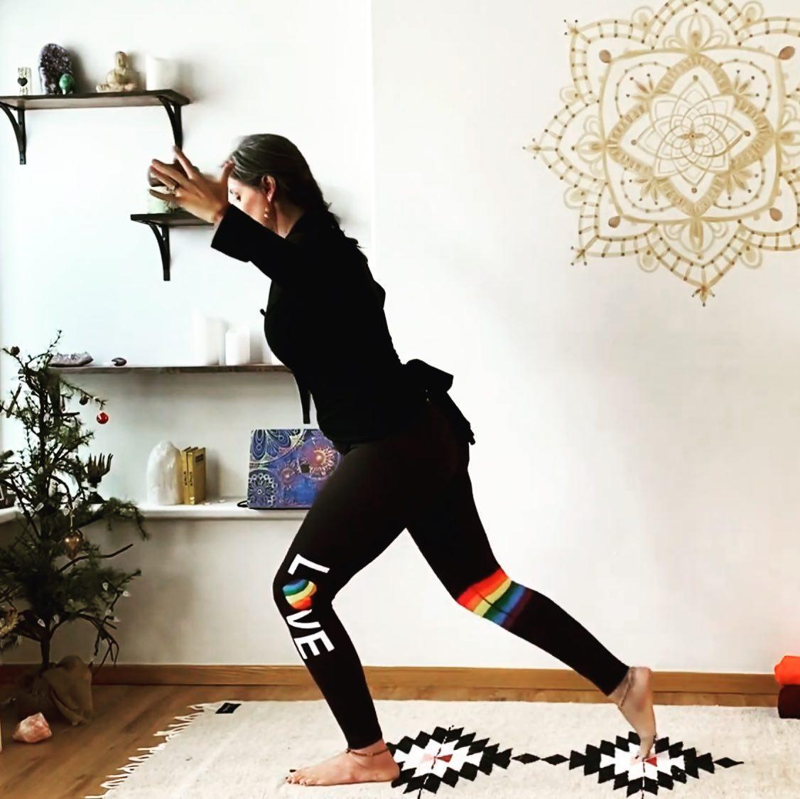 Mindful Movement with Danica Lynch from Yoga Yoga, photo of a woman doing yoga with a black athletic wear that spells LOVE with a rainbow stripe across her calf