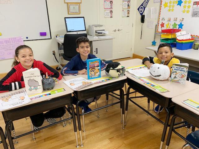 Three students seated at desks display the books they read and the pumpkins they decorated
