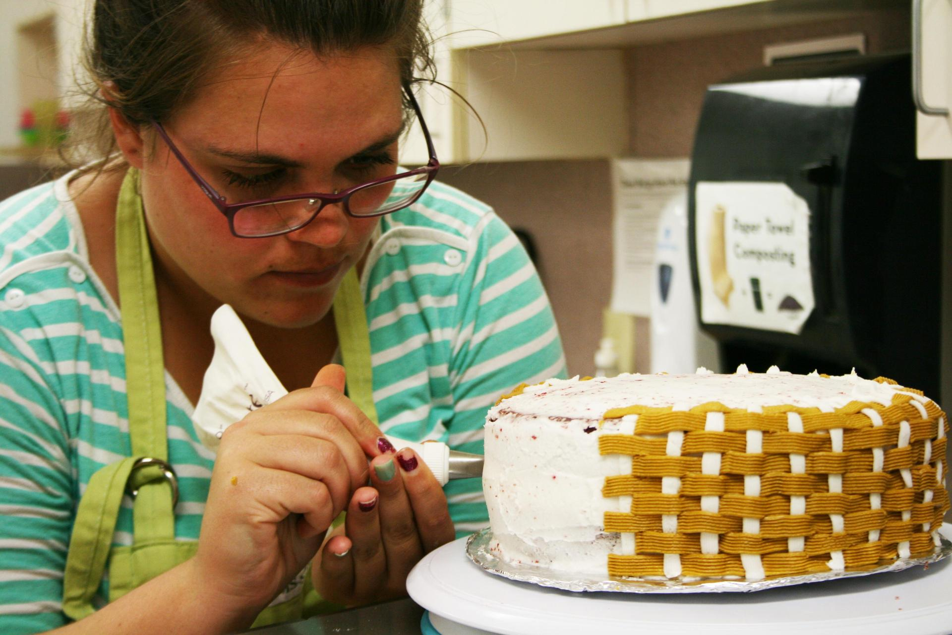 An adult student using a piping bag to decorate a cake with a basketweave pattern.