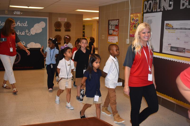 students and teacher in school hallway