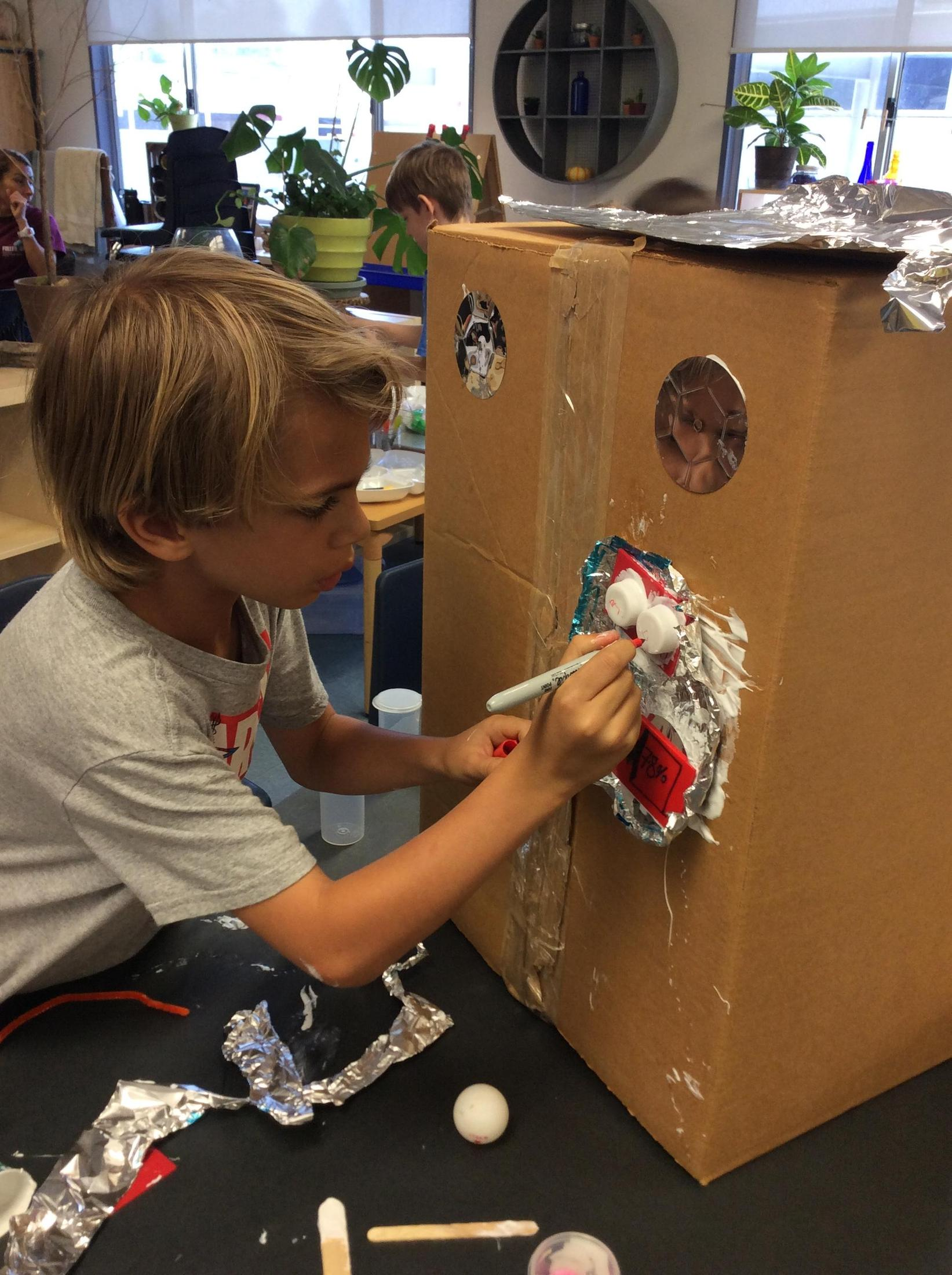 Children are using recycled materials to design cardboard robots.