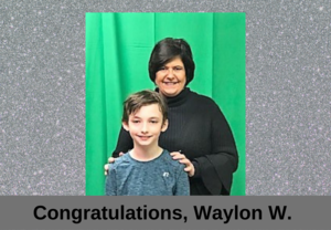 boy standing with woman in front of green screen