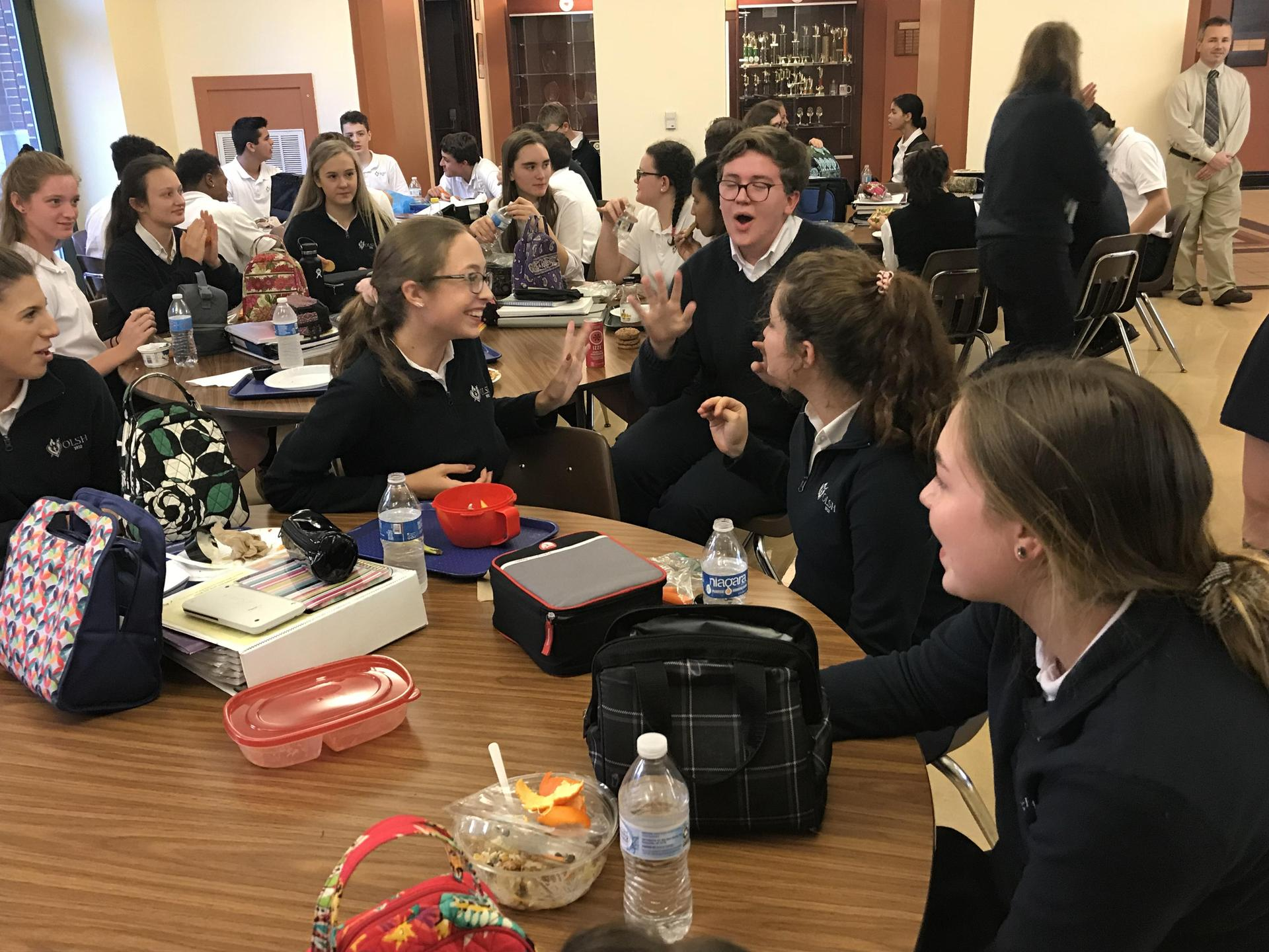 Brenna enjoys lunch with friends in the OLSH cafeteria.