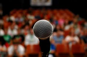 An image of a microphone with a blurred audience in the background.