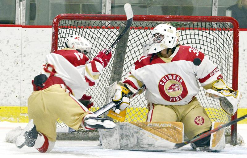 An EHS player sprawls to clear the puck away from in front of his goalie