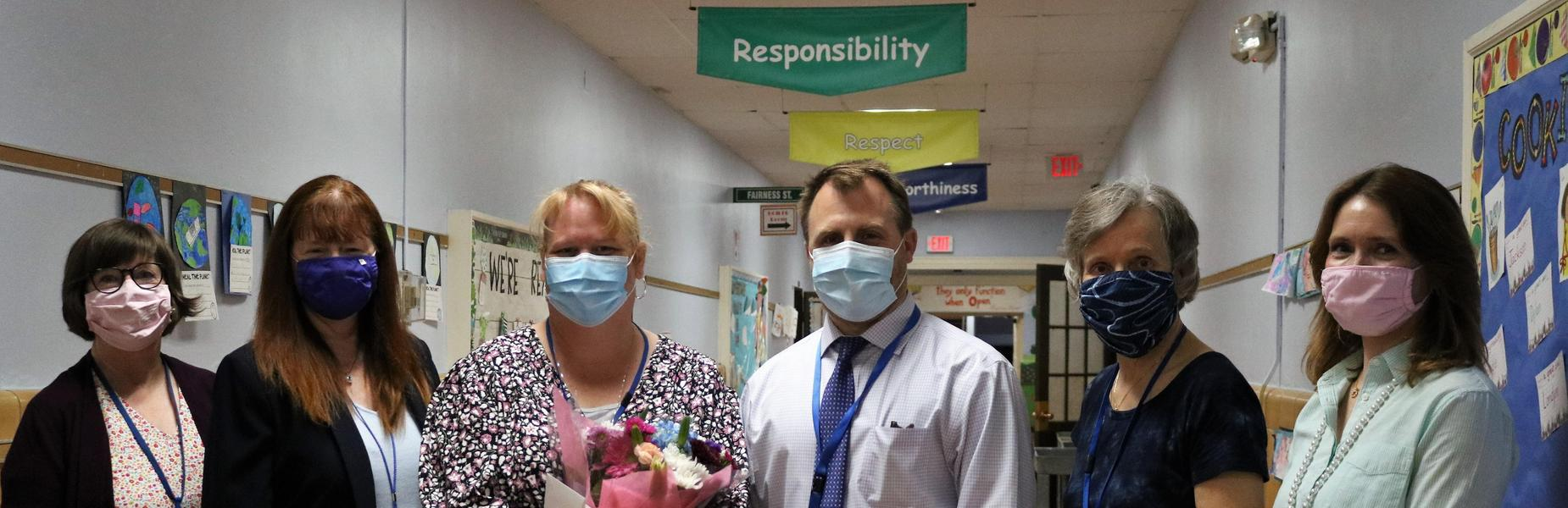Photo of 2021 Philhower Fellow Nancy Rygiel, holding flowers and posing for a picture with superintendent, principals, and secretaries at Frankin.