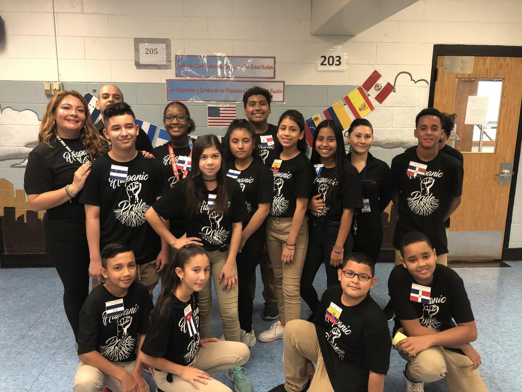 Mrs. Ramirez and aide with her class all wearing black hispanic pride shirts