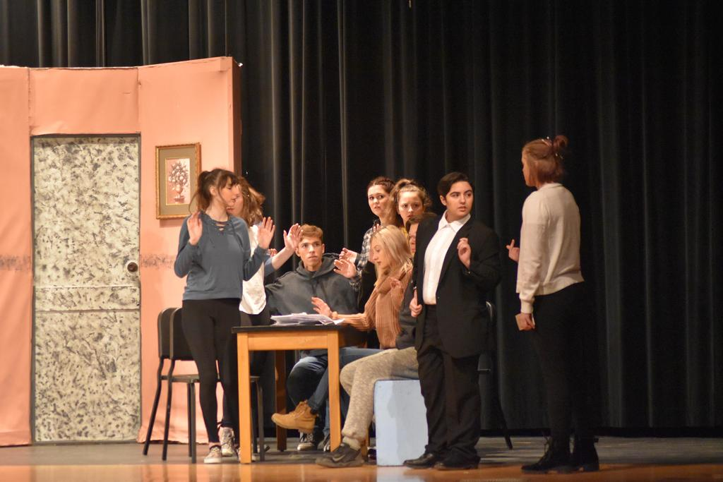 Students performing on stage in a play