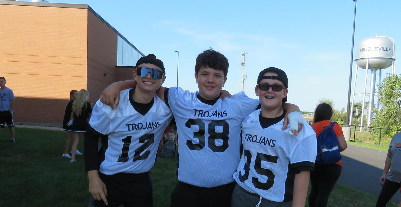 Three middle school football players pose for a photo at the homecoming parade.