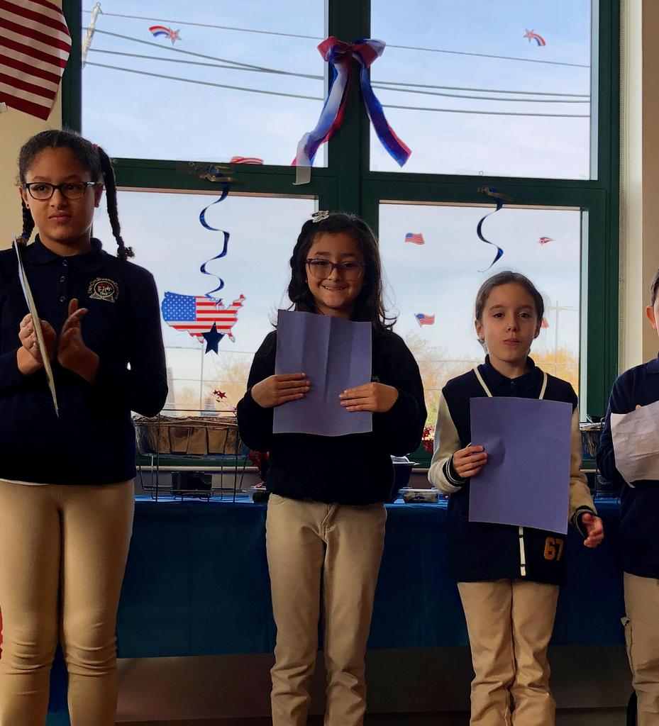 three happy girls standing with their letters for the veterans at the breakfast