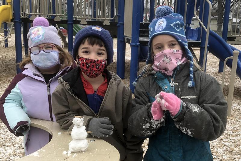 Children on playground with small snowman