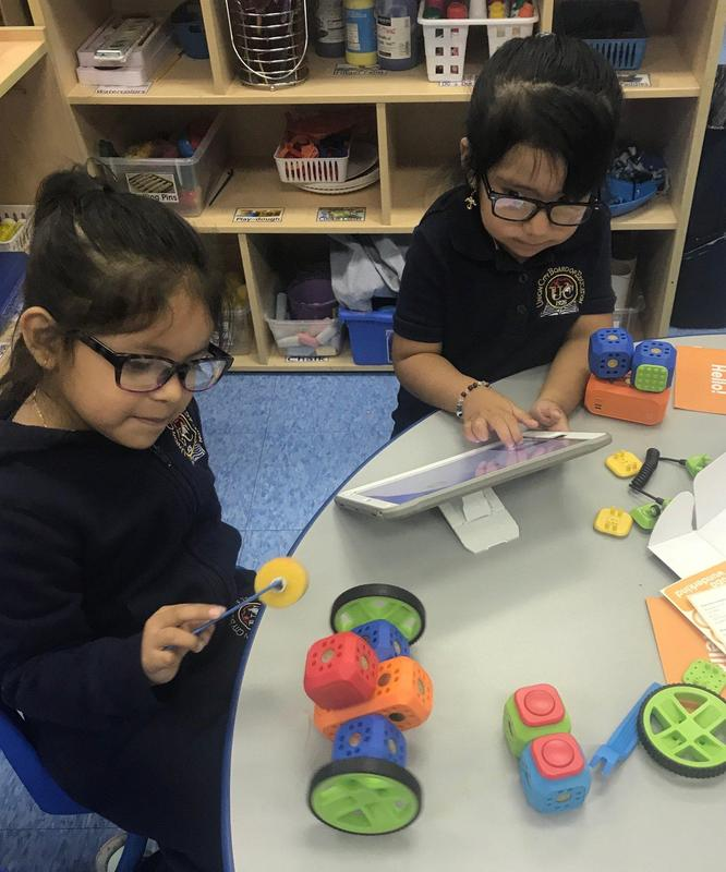 two little girls with glasses seated at a table.  One girl working on an ipad and the other holding a round tool about to touch a robot they just created