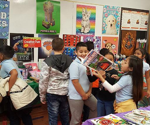 group of students at Scholastic Book Fair, three in the centre hover over a book.