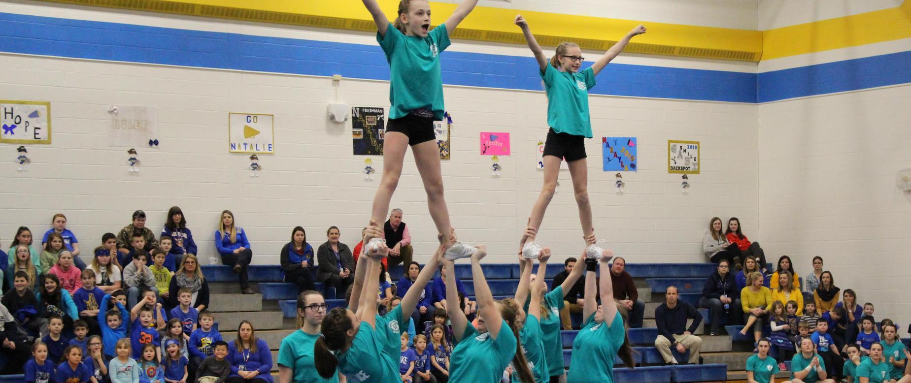 cheerleaders perform trick as crowd looks on