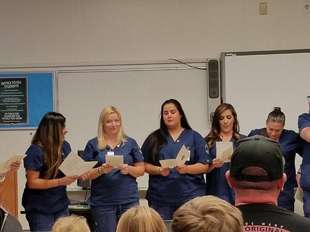 Group photo of CNA students reciting CNA pledge during graduation
