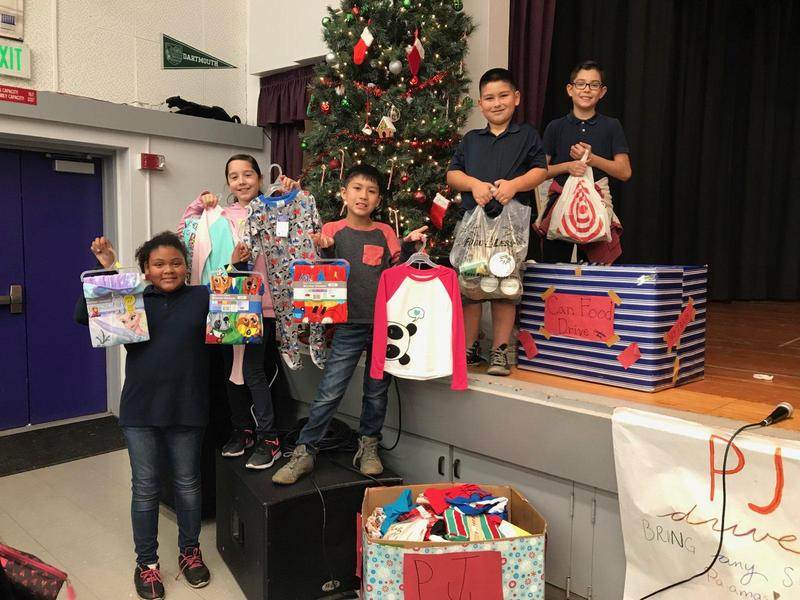 Students pose with pajamas and cans that were donated by staff and students.