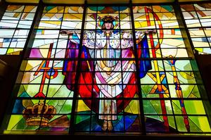Stained glass window of Christ on the cross above entrance to Christ the King