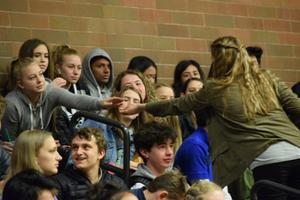 teen girl handing something to girl sitting in gym bleachers. each has a hand outstretched to the other, but their outstretched hands are still about six inches away from one another