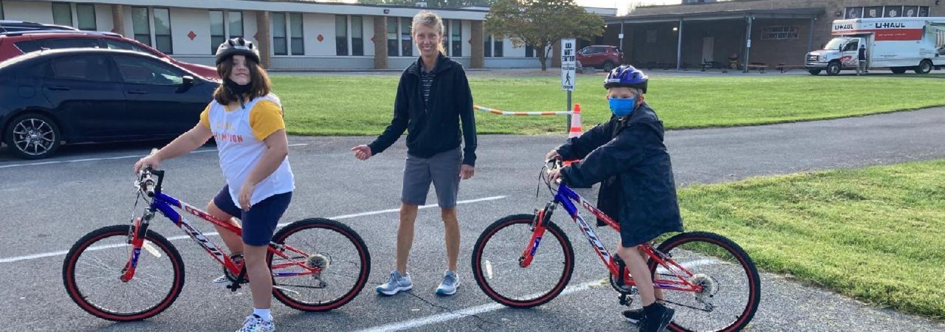 Photo of Mrs. Burchett, PE teacher, and two students riding bikes