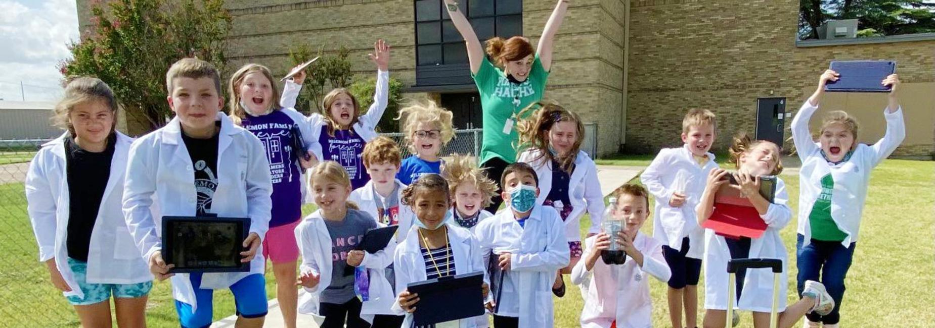 young students wearing lab coats jumping with their teacher