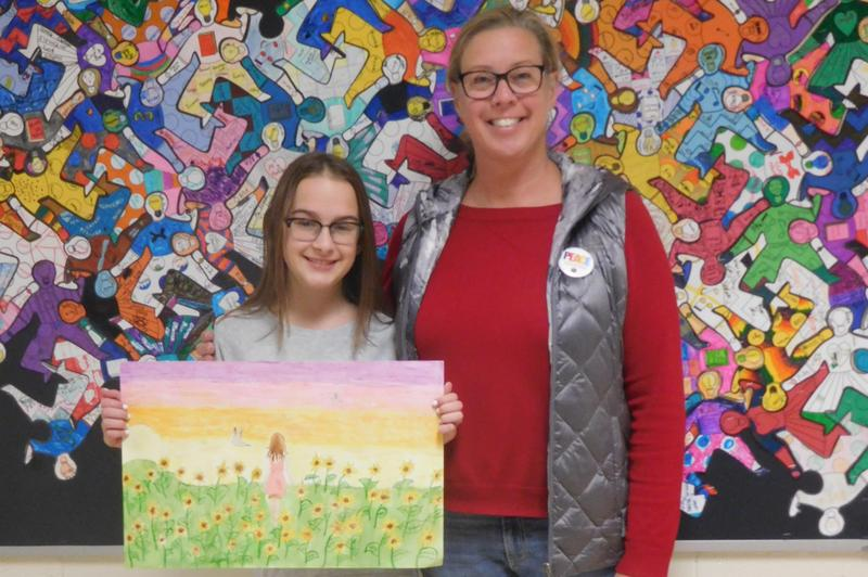 Riley, contest winner, holds up her winning poster with art teacher Mrs. Ernstes