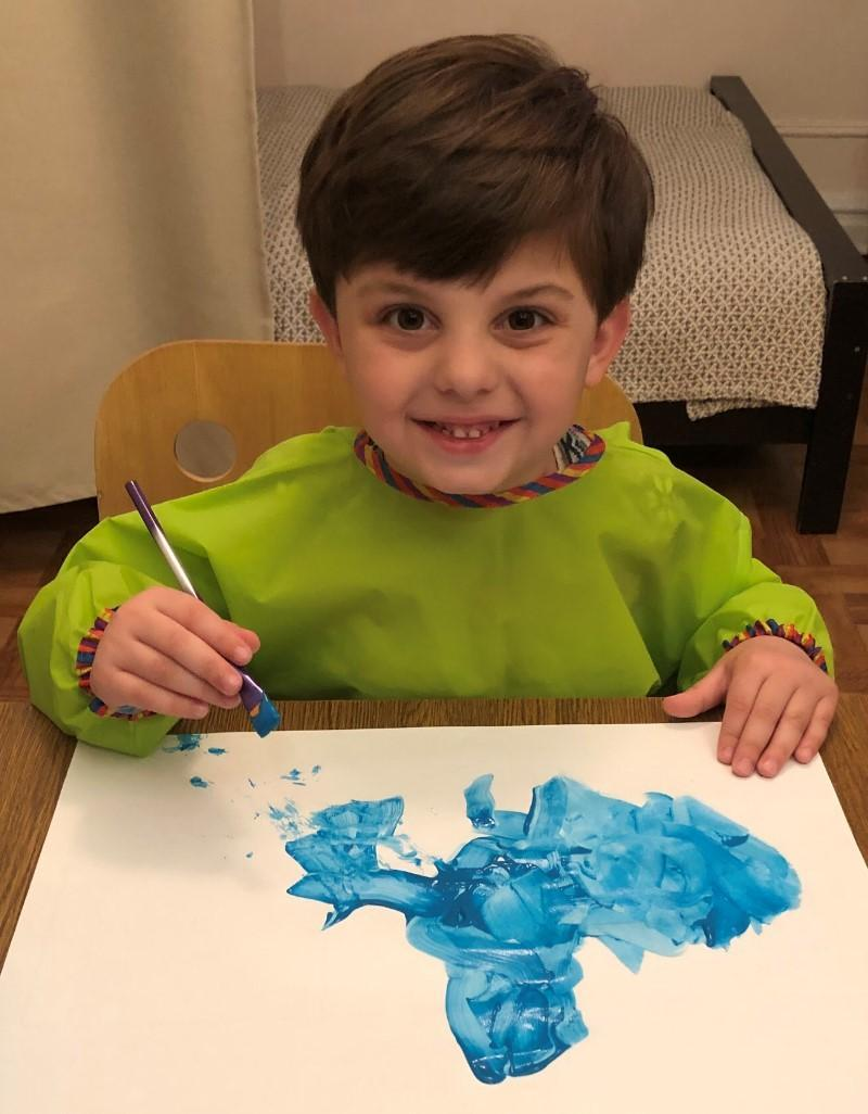 Student at home during remote learning. He is painting with blue paint on canvas.