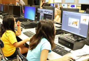 Two STEM campers work on Scratch Programming on computers during STEM Camp.