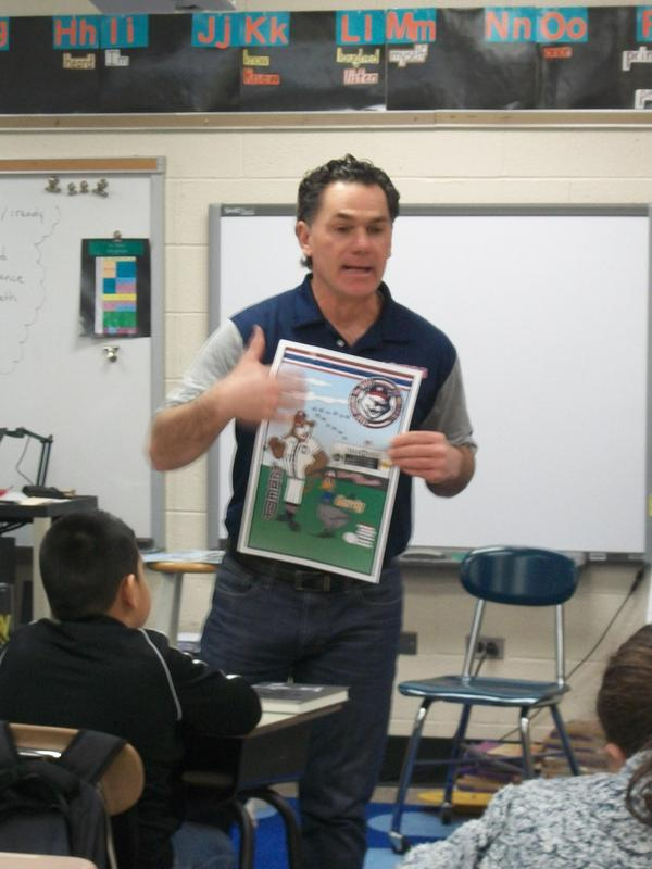 Greg Suire holds the Hi-Tom's poster and explains the reading program to students.