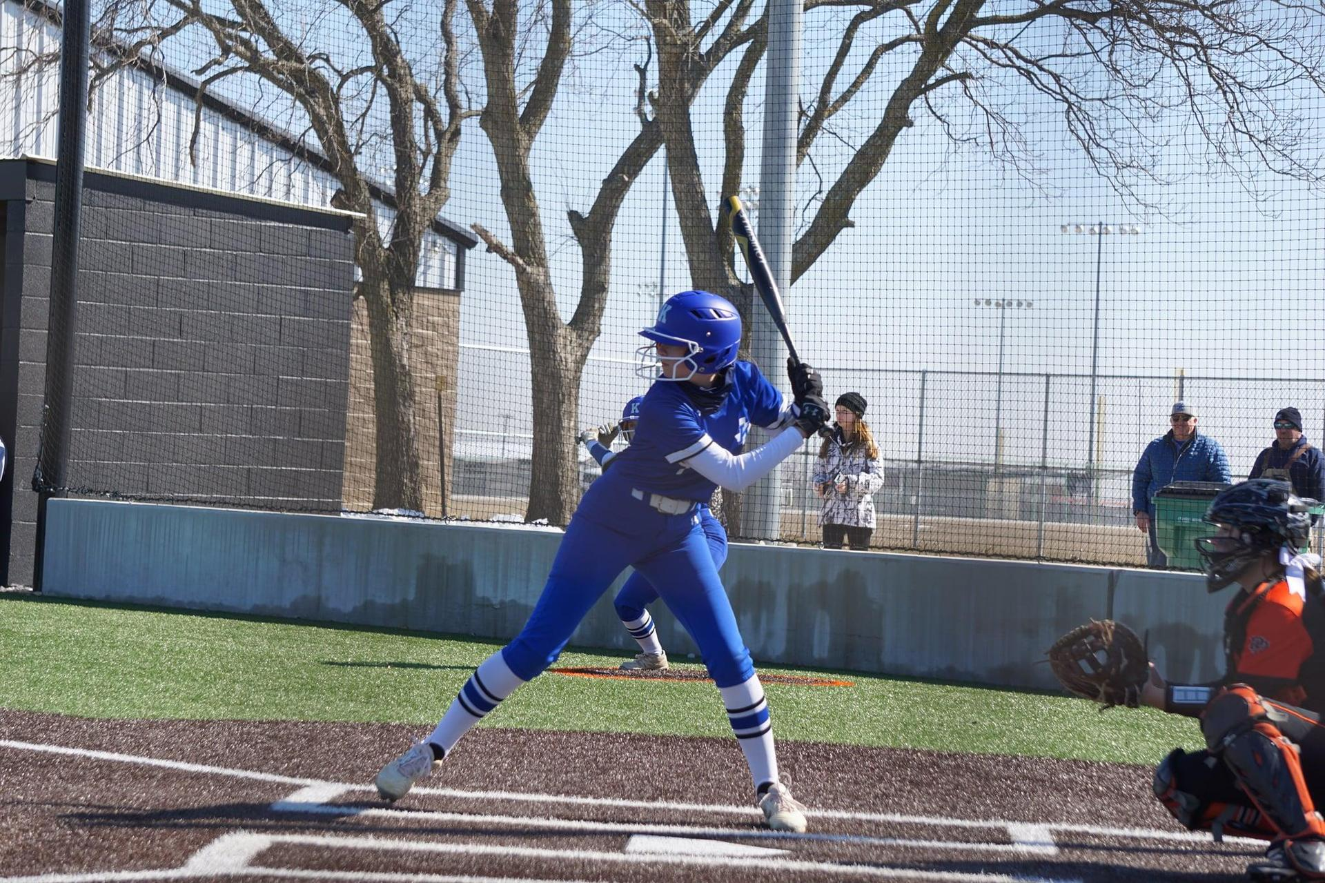 a softball player in all blue steps up to the plate ready to swing the bat