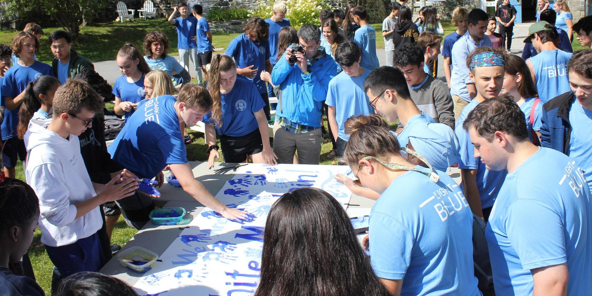 Students placing painted Dark and Light Blue handprints on an all-School banner.