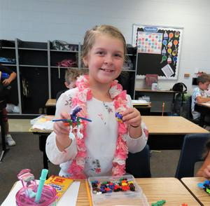 A 4th-grade girl holds up her unique creations.