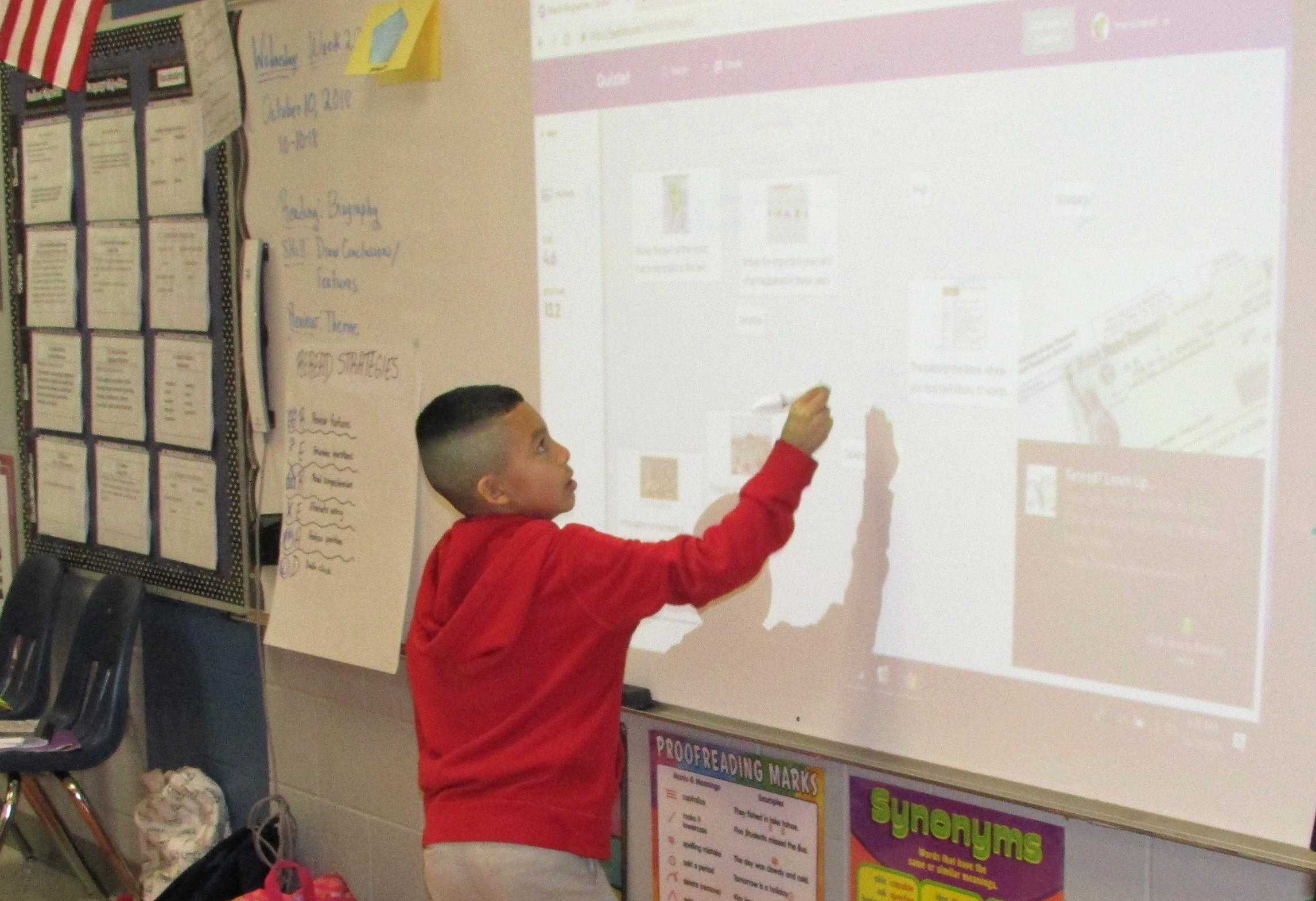 3rd grade student using interactive board