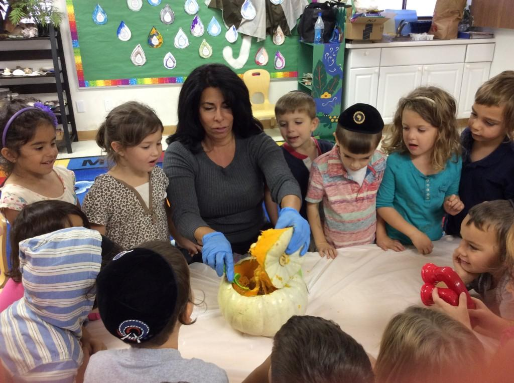 teacher carving a pumpkin with students watching