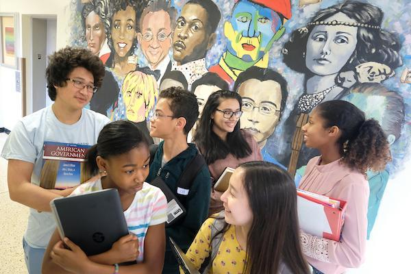 Students with books in front of school mural.