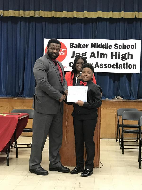 Baker Middle School Principal, Mr. Walker, presenting certificate to newest JAG member at induction ceremony