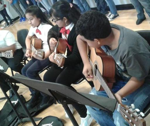 5th Grade Guitarists on stage performing, sitting on chair playing guitars.