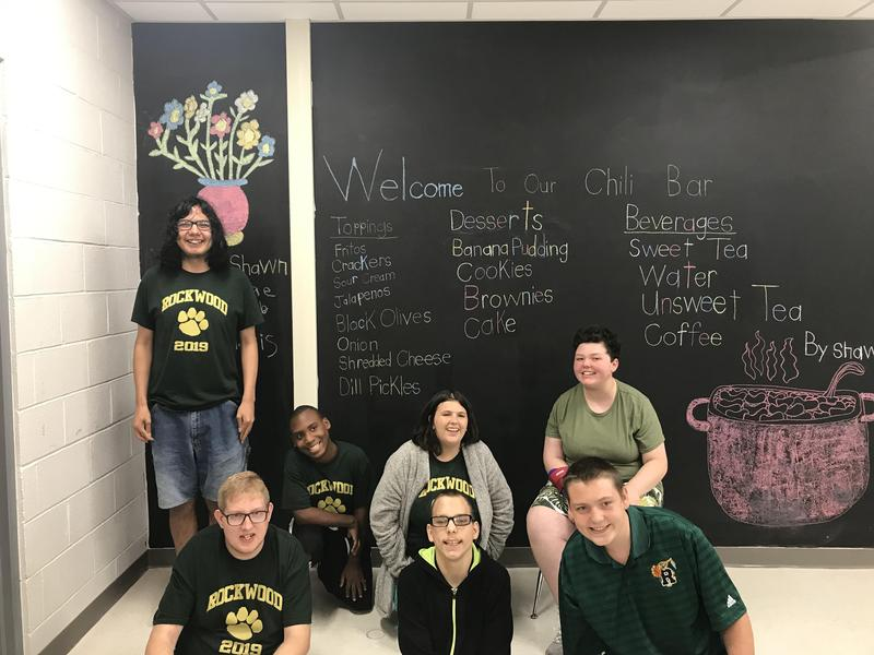 Students in from of Chili Bar welcome banner with menu items
