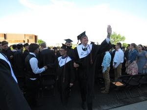 A graduate waves to family and friends after the ceremony.