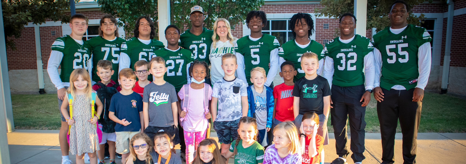 young students with varsity football players